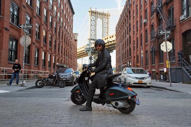 Hombre conduciendo una Vespa Armani en la calle de la ciudad de Nueva York.