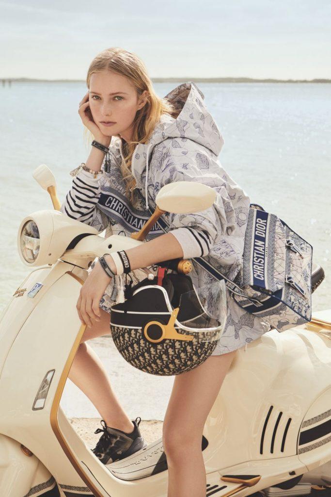 Mujer sobre el scooter Dior con Casco y bolso edición especial.