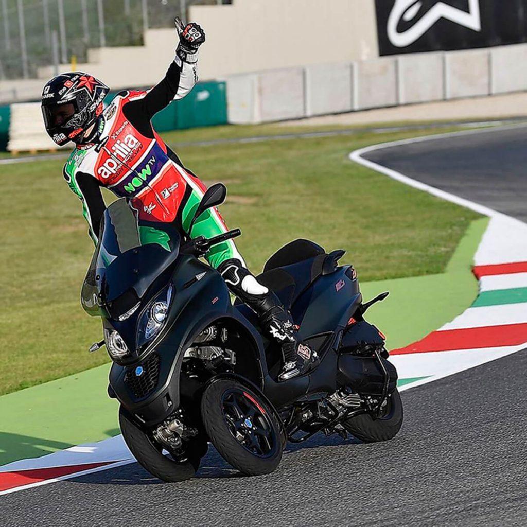 Piloto de Aprilia Racing conduciendo un Scooter Piaggio MP3.