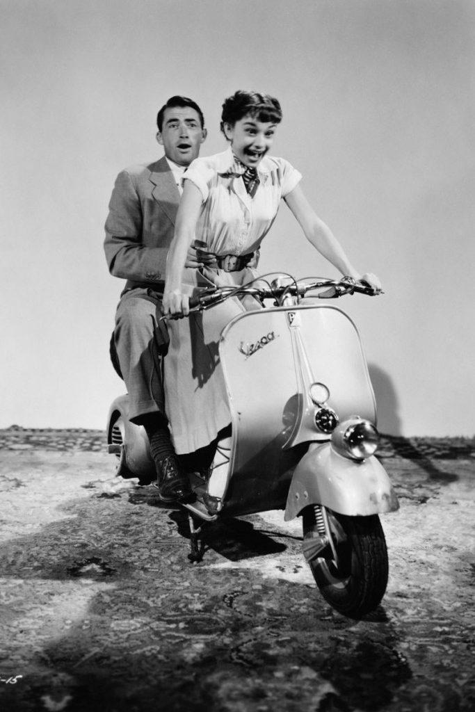Foto antigua de Audrey Hepburn y Gregory Peck conduciendo una Vespa blanca.